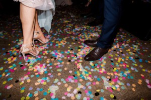 A bride and grooms feet in beautiful shoes standing on colourful confetti on the dancefloor at a wedding