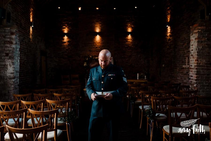 groom in soldiers uniform in barn wedding venue reading note