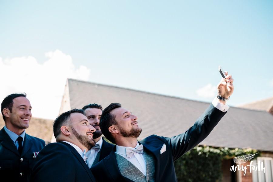 amy faith photography creative documentary wedding photographer groomsmen taking selfie at farm wedding venue