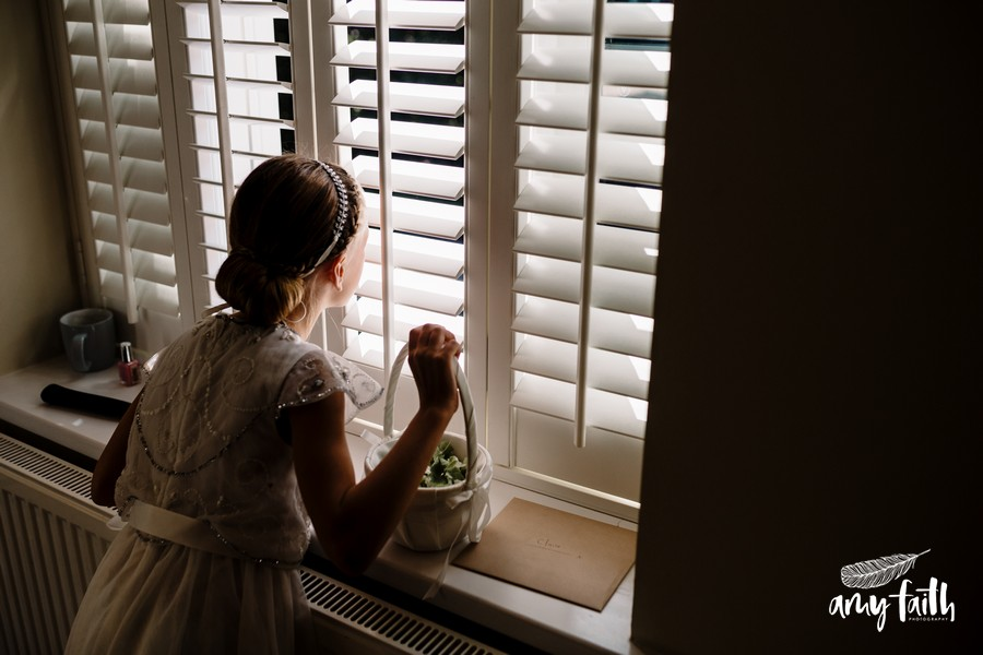 creative documentary wedding photographer little flower girl in white dress looking out window