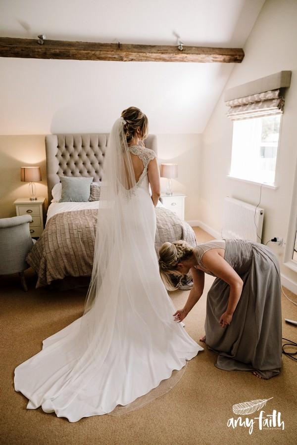 creative documentary wedding photographer bride in modern dress with bridesmaid fixing train