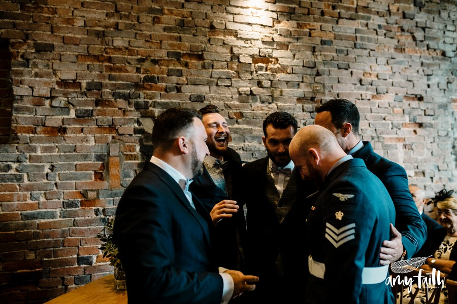 creative documentary wedding photographer laughing groomsmen in soldiers uniforms