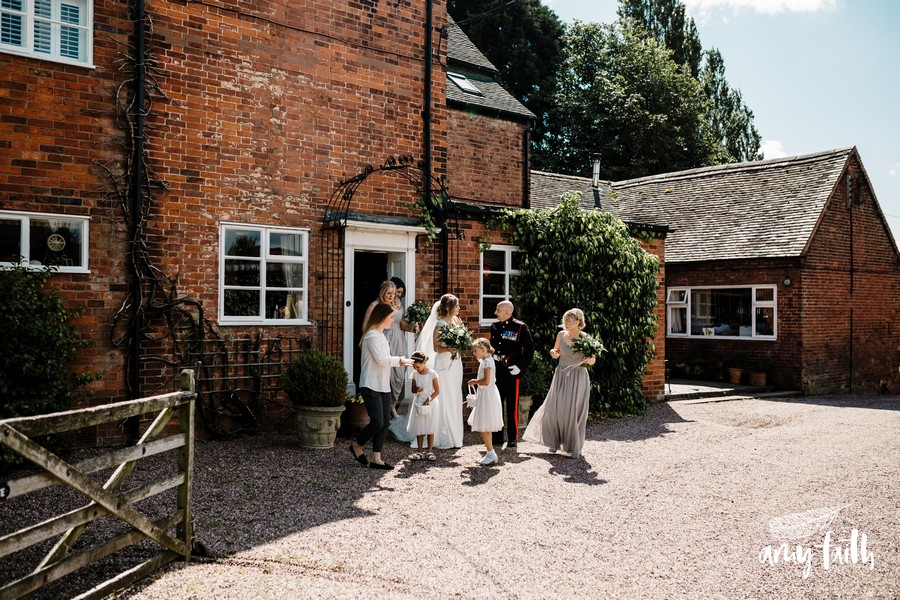bride leaving farm house with bridal party in sunshine