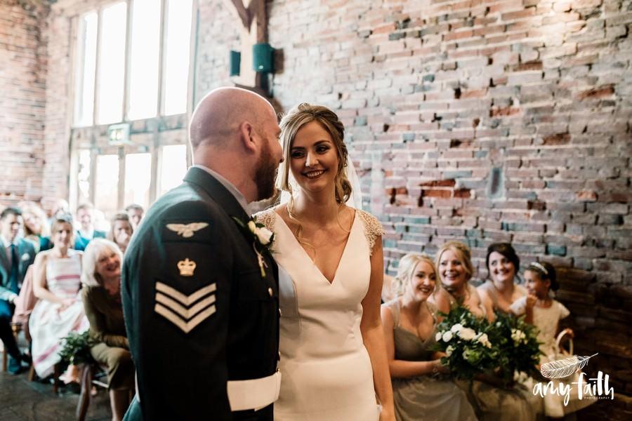 Smiling bride in mdoern wedding dress looking at groom in soldiers uniform in farm wedding venue