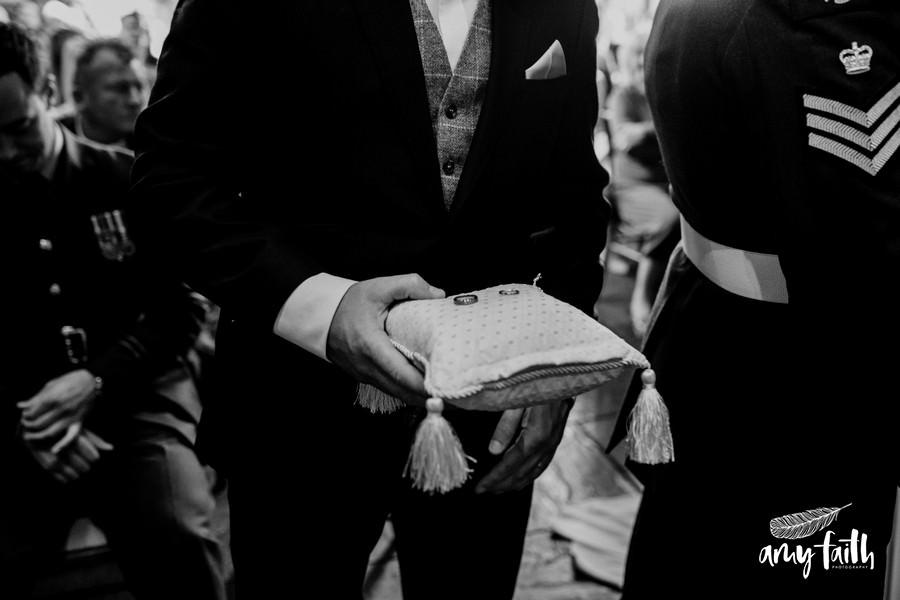 Black and white portrait of best man holding wedding rings on tassled cushion