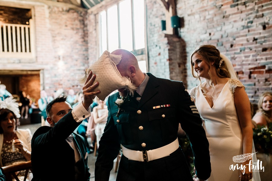 Best man jokingly wiping grooms head with ring cushion as bride smiles