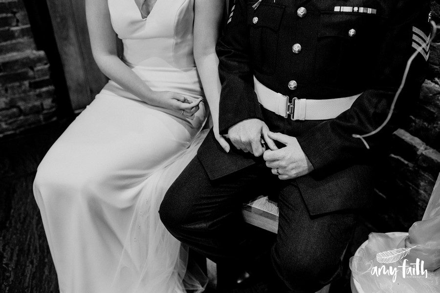 Black and white close up of groom holding brides hand as they are sat down