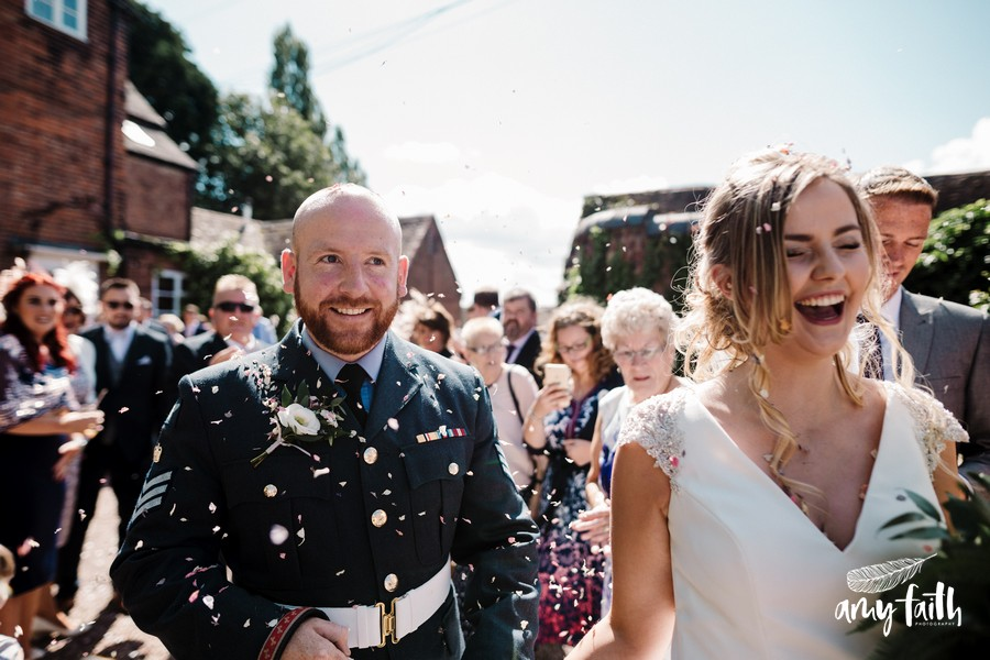 Really happy bride and groom during a confetti throw in the sunshine