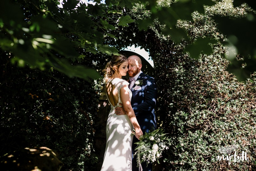 Groom holds brides waist as she shows off her modern wedding dress in dappled light from sun through trees