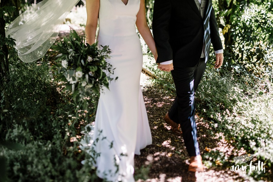 Close up shot of bride and groom walking hand in hand through garden with veil blowing