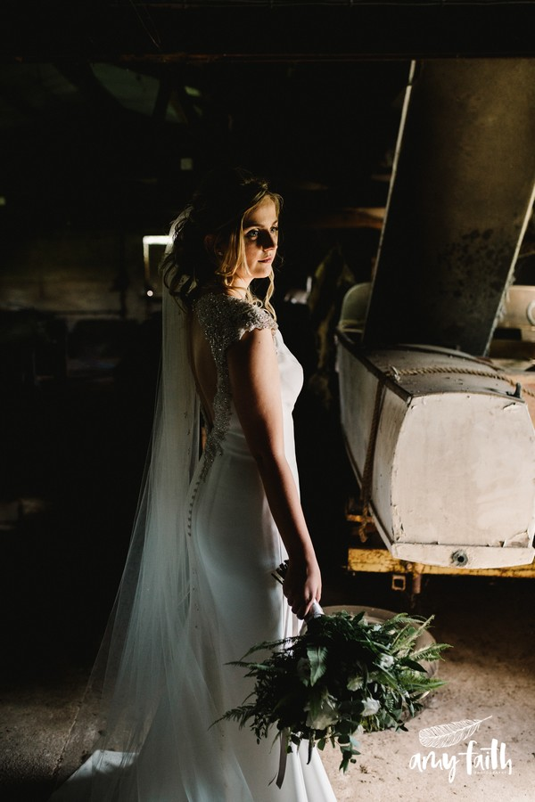 Bride in modern wedding dress lit by soft light while holding bouquet next to an old motorboat