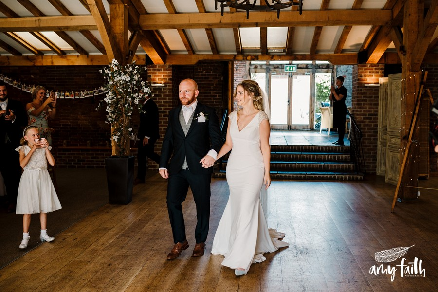 Bride and groom enter converted barn wedding venue holding hands and smiling