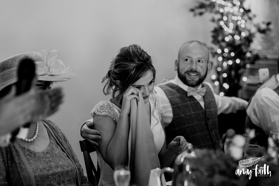 Bride wiping her tears with a napkin at her fathers speech