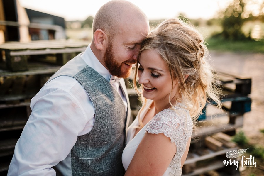 Smiling bride and groom with closed eyes and heads together in sunset light by wooden pallets