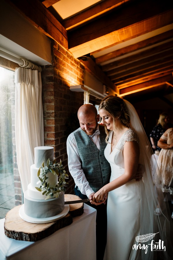 Bride and groom smiling and cutting marbled iced wedding cake in window light
