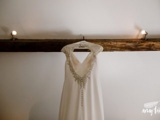 beautiful beaded white wedding dress hanging from beam