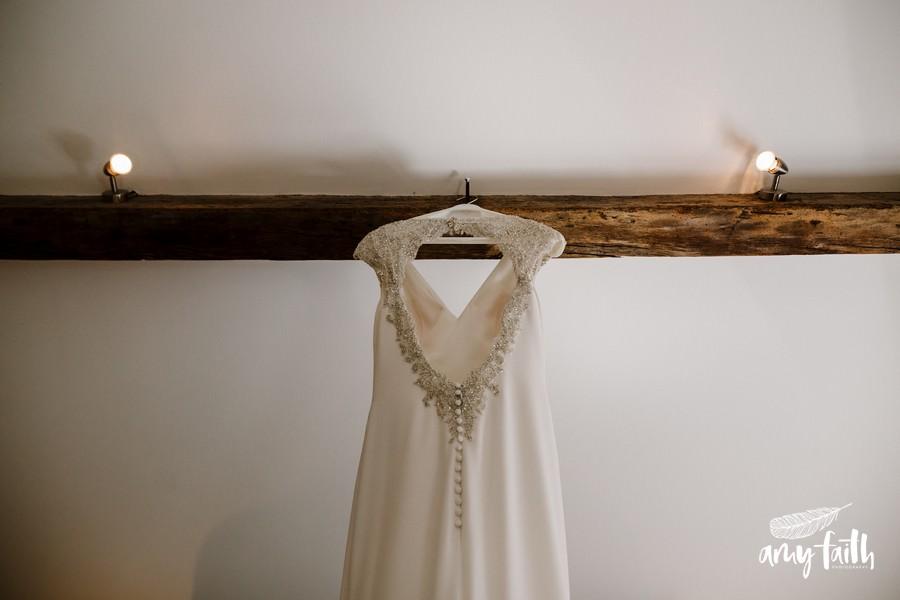 beautiful beaded white wedding dress hanging from beam