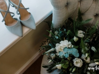blue bridal shoes with a green bouquet on a grey chair