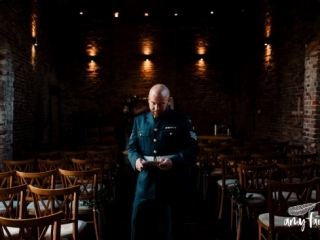 groom in soldiers uniform in barn wedding venue reading note