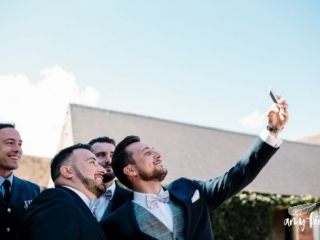 amy faith photography creative documentary wedding photographer groomsmen taking selfie at farm wedding venue