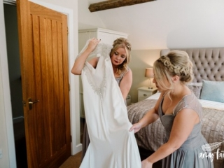 creative documentary wedding photographer bridesmaids helping with white wedding dress during bridal prep