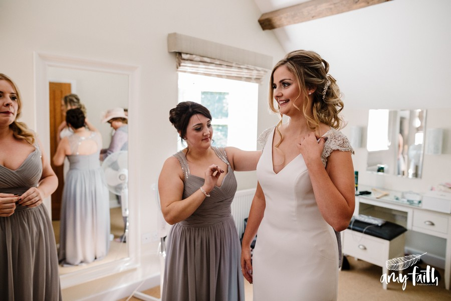 creative documentary wedding photographer smiling bride in modern dress in white room with bridesmaids