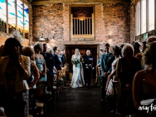Bride walking down aisle in farm barn with father in modern wedding dress