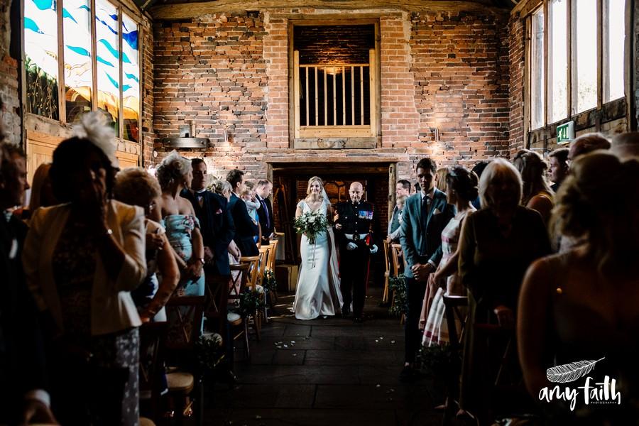 Bride walking down aisle in farm barn with father in modern wedding dress