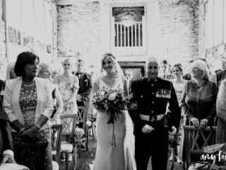 Smiling bride in modern dress and proud father in soldiers uniform walking down aisle in farm wedding venue