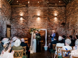 Bride and groom have their first kiss as guests watch in a quirky converted farm venue with brick walls