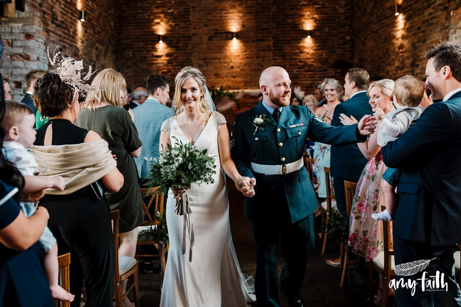 A happy bride and groom make their way back down the aisle as they say hello to some guests
