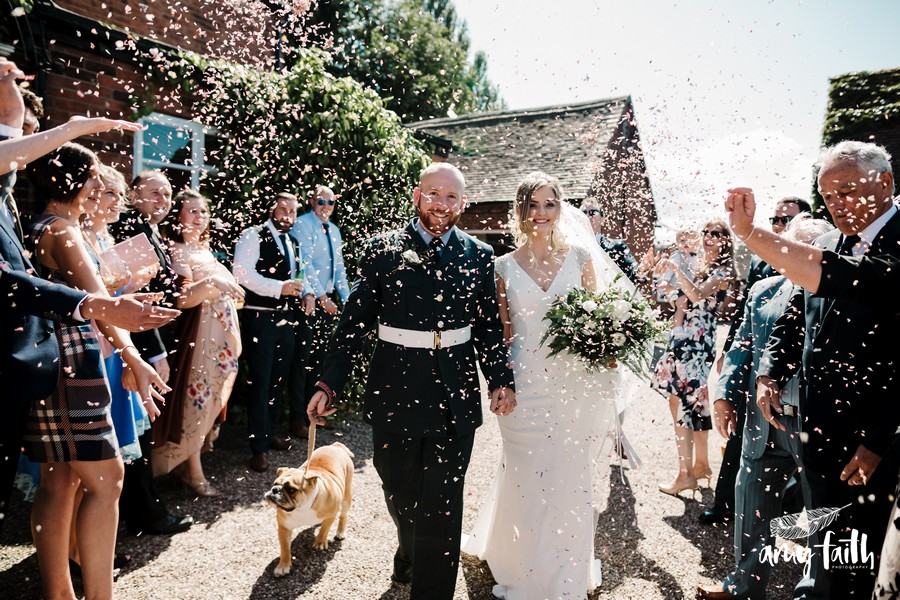 Bride and groom with their bulldog walking through a group of smiling guests as they throw confetti everywhere in the sunshine