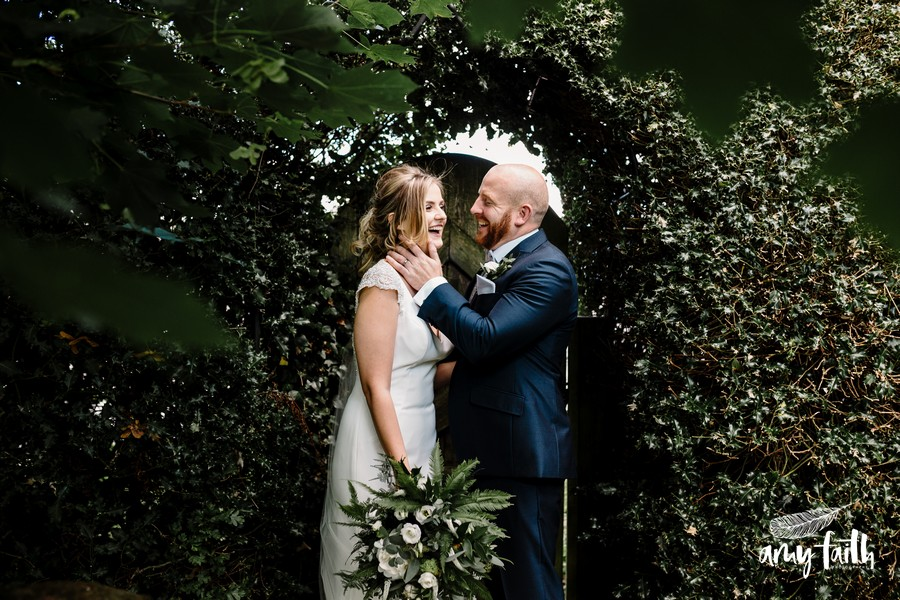 Groom smiles as he holds his happy brides face while they stand near a bush