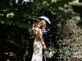 Groom holds brides waist as she shows off her modern wedding dress in dappled light from sun through trees
