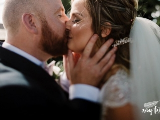 Close up of groom holding brides face gently as they kiss in the sunshine
