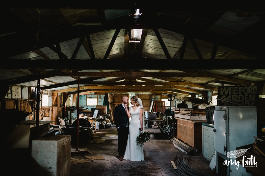 Bride holds her hand up to the grooms face as they stand side by side in soft light through the roof of a derelict farm shed creative wedding photography