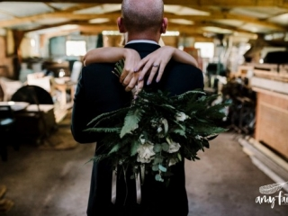 Brides arms and bouquet lay over grooms shoulders as picture is taken from the back of the grooms head.