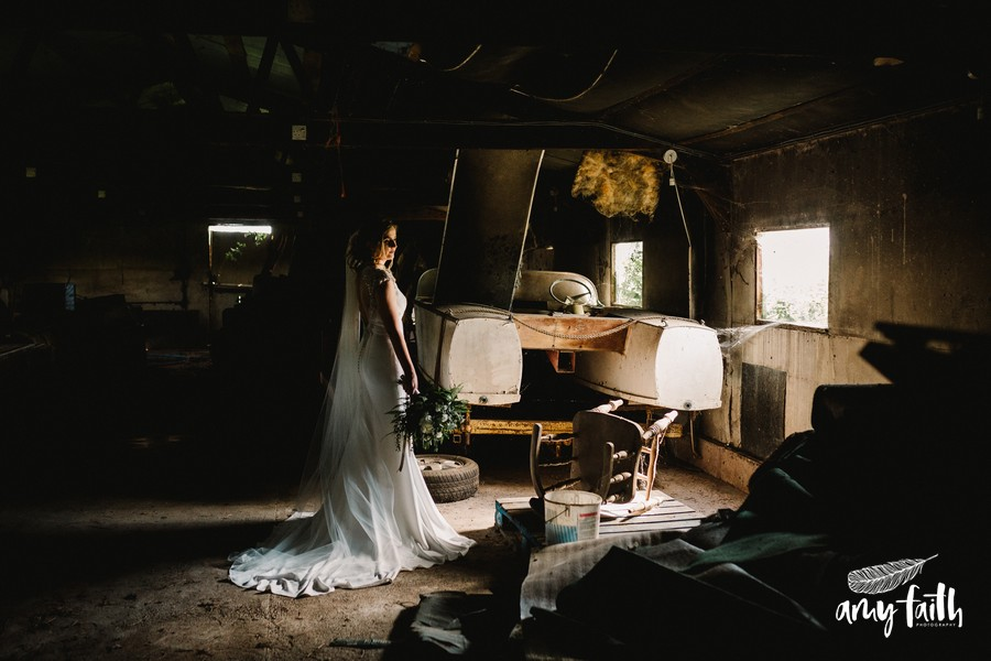 Bride in modern white wedding dress standing in soft light through window in derelict shed next to an old motorboat and surrounded by dust creative photography
