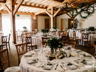 Wedding tables with white tablecloths and green foliage with wooden chairs in bright converted barn space