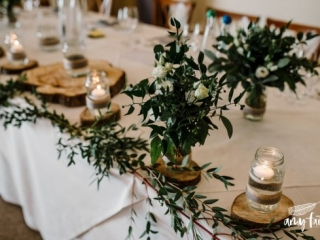 Modern green foliage centrepieces on white tables with wood slices and candles