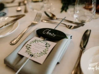 Modern wedding place setting with guests name written on leaf with sparkler attached