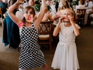 Two little girls using funny face cards and waving their arms about being silly in wedding venue