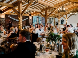 Wedding guests laughing at smiling at speeches while sitting at tables in converted barn
