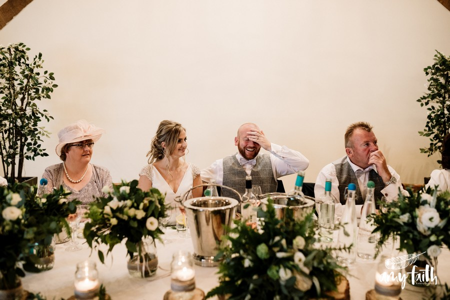 Groom on top table laughing at speeches and holding his head