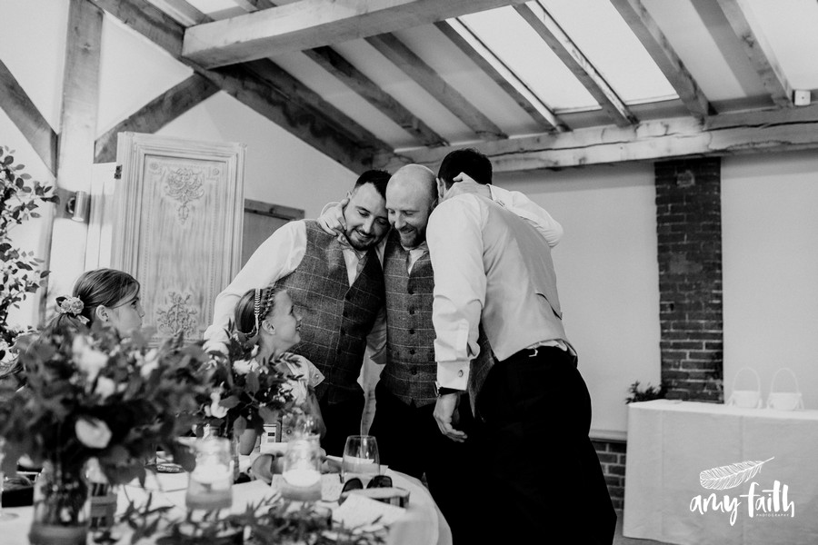 A smiling groom hugging his two best men after their speeches