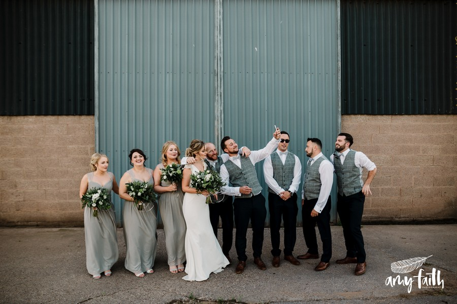 Bridesmaids and groomsmen and bride and groom standing in a line in front of a grey barn door while one takes a selfie