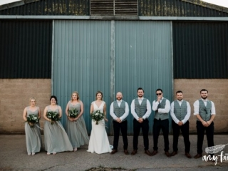 Bride groom bridesmaids and groomsmen standing in a line outside a farm barn grey dresses grey waistcoats