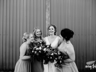 Laughing bride and her bridesmaids with bouquets in black and white