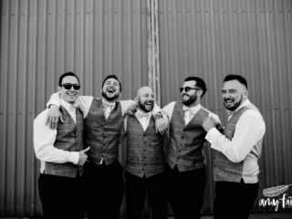 Laughing groom and groomsmen with their arms around each other in black and white