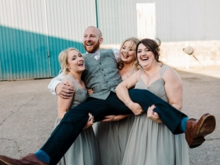 Laughing groom lifted by three bridesmaids with his legs wide open on sunny wedding day